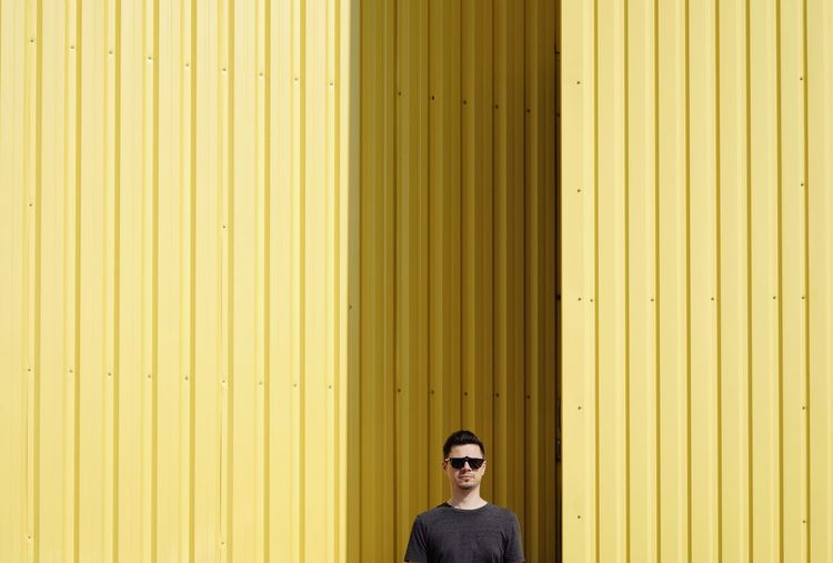 Portrait Of Man Wearing Sunglasses Against Yellow Corrugated Iron