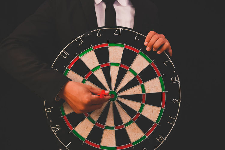 Midsection of businessman with dartboard standing against black background