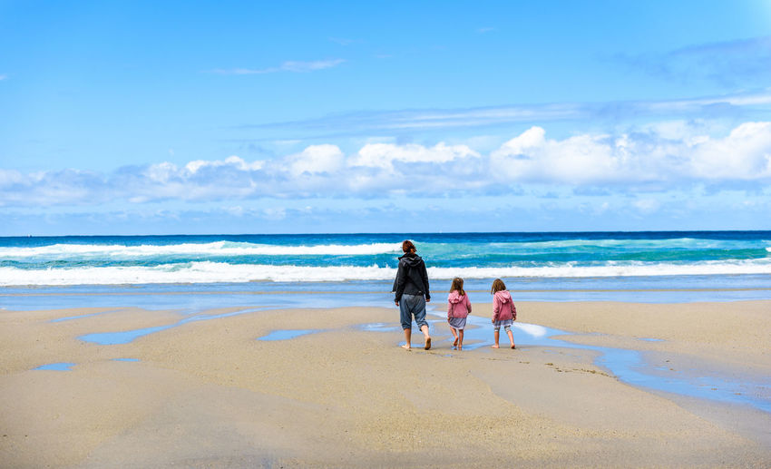 Rear view of woman with daughters walking at beach