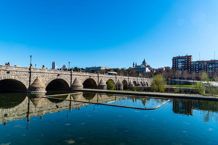 Arch bridge over river against blue sky