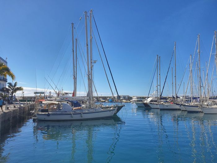 Sailboats in marina at harbor against clear blue sky