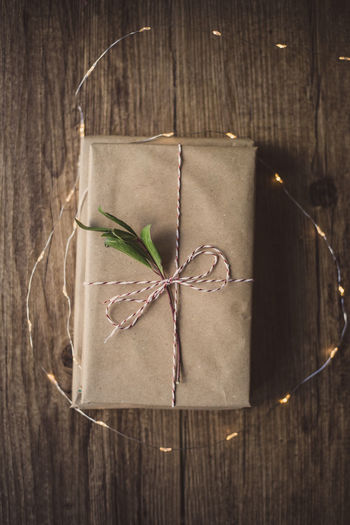 Wrapped gifts on wooden table Gift Gifts ❤ Present Wrap Wrapping Paper Wrapping Cozy Christmas Birthday Christmas Holiday Love Wrap Chritsmas Decoration Gift Paper Wrapped Close-up Tying Tied Up Dried Plant Leaf Freshness Day Table Wood - Material