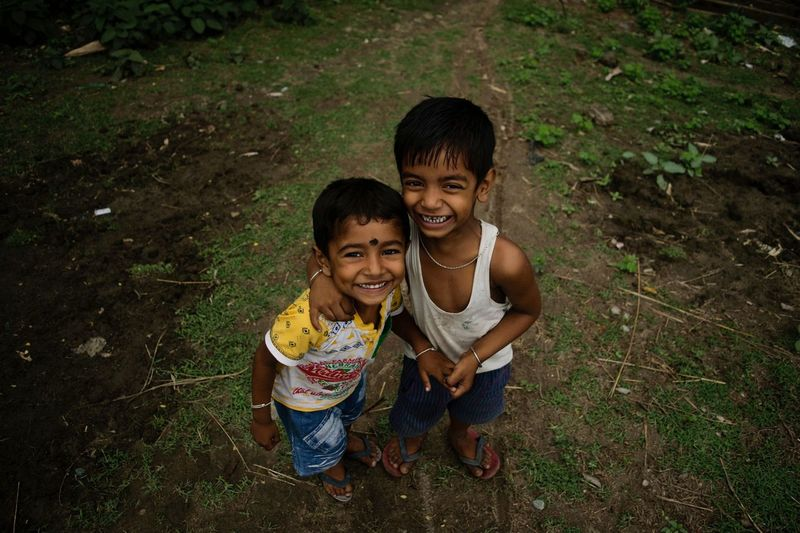 High Angle Portrait Of Smiling Siblings Standing On Field