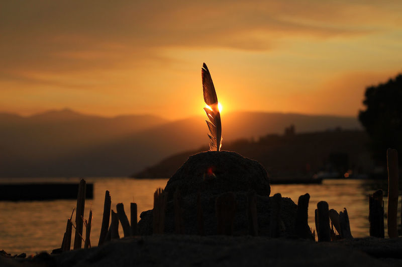 Sand castle at shore of lake chelan against sky during sunset