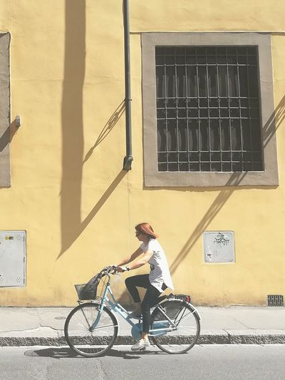 Woman riding bicycle by building