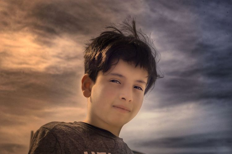Portrait of boy against sky during sunset