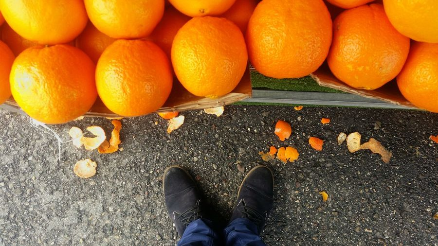 Low Section Of Man Standing By Oranges On Market Stall