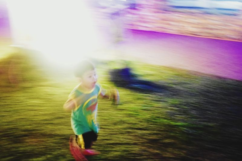 Full length of young woman running on grass