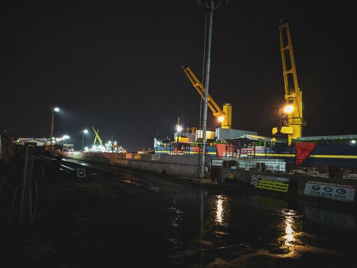 Illuminated pier at harbor against sky at night