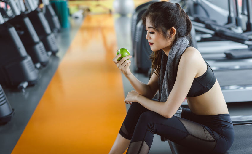 Woman Holding Granny Smith Apple While Sitting On Treadmill In Gym
