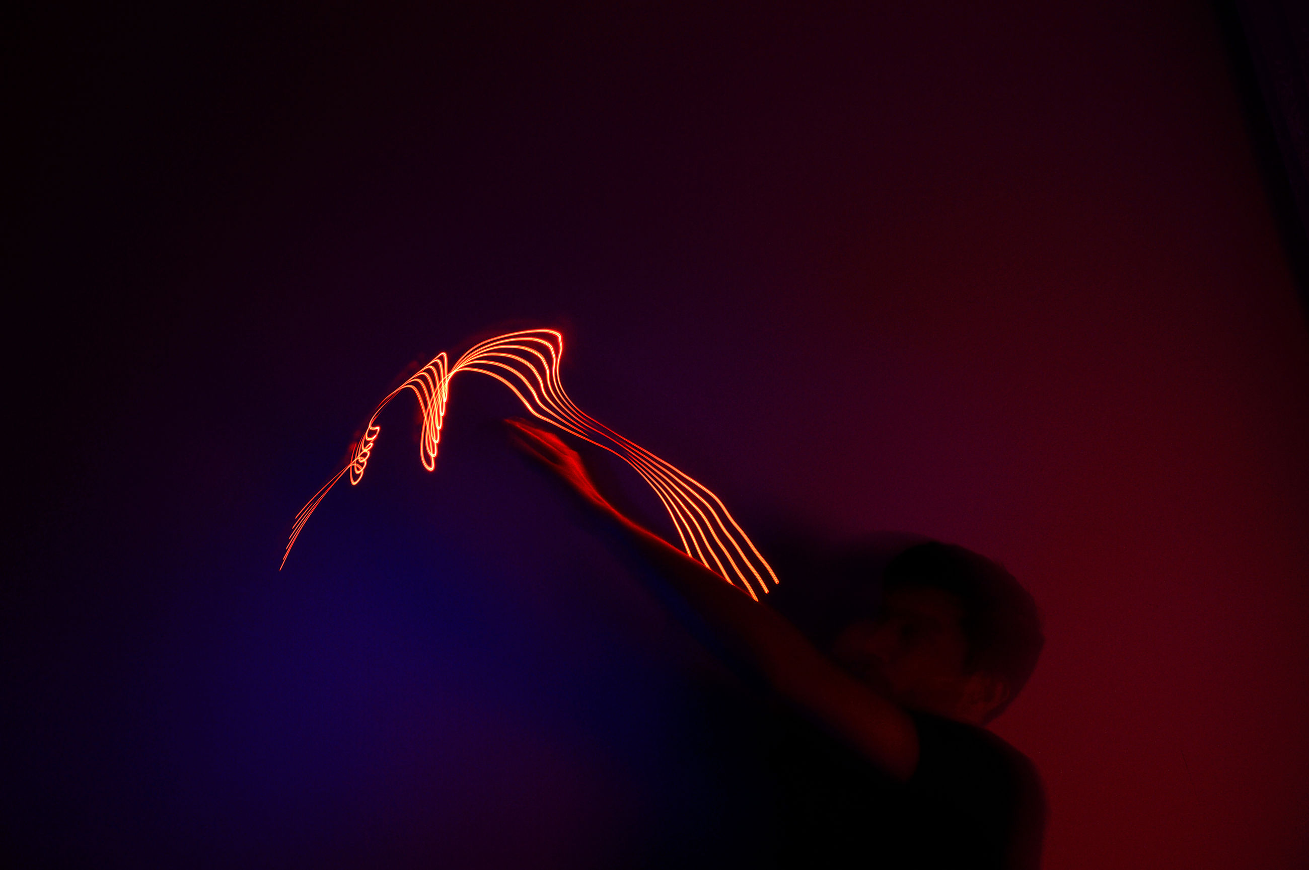 copy space, one person, red, illuminated, long exposure, motion, indoors, studio shot, glowing, close-up, hand, human hand, leisure activity, light painting, lifestyles, night, low angle view, cut out, blurred motion, black background
