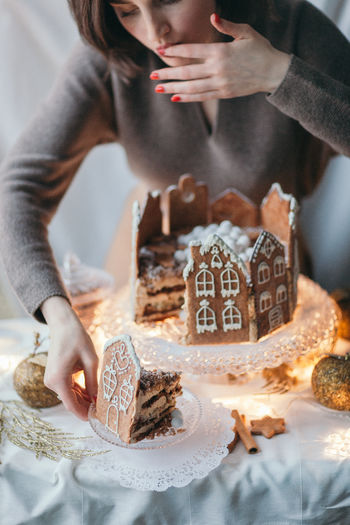 Sweet Food One Person Indoors  Sweet Women Dessert Baked Celebration Food Food And Drink Cake Real People Event Christmas Focus On Foreground Holding Chocolate Number Temptation Gingerbread Gingerbread House Homemade Cake Piece Of Cake Tasting Lifestyle