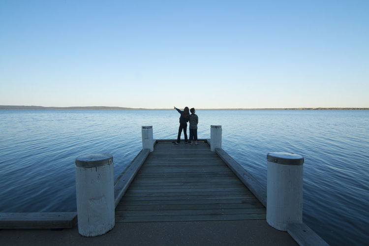 Rear view of men standing on pier against clear blue sky