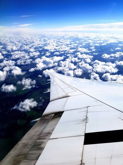 Aerial view of airplane wing against blue sky