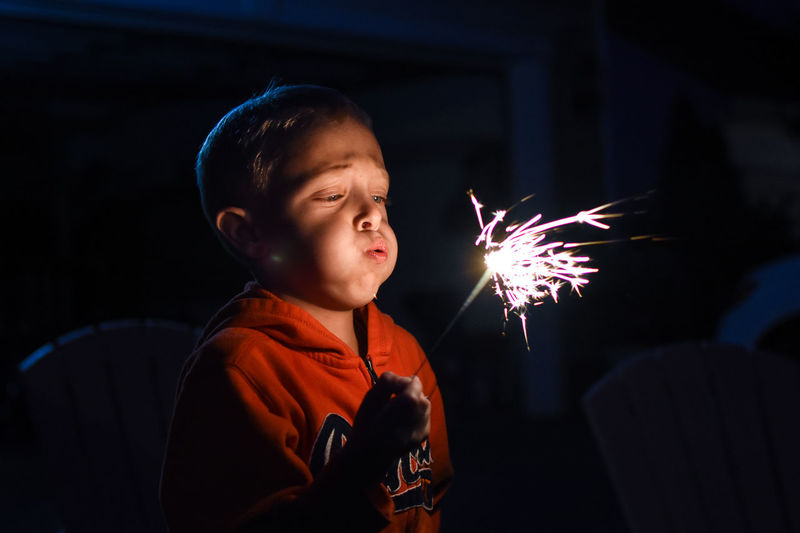 Close-up of boy blowing sparkler