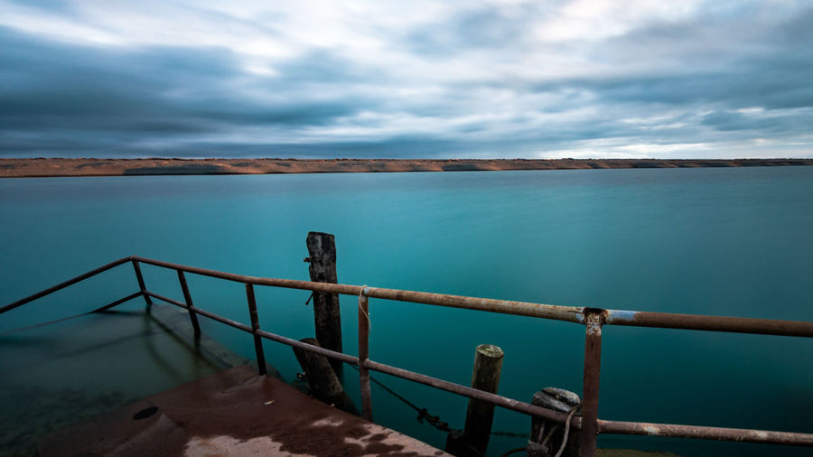 Beauty In Nature Blue Cloud - Sky Cloudy Day Long Exposure Longtimeexposure Nature No People Non-urban Scene Railing Scenics Sky Water Water Reflections