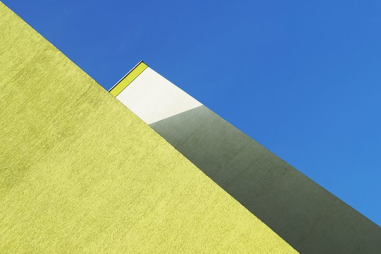Low Angle View Of Yellow Wall Against Clear Blue Sky