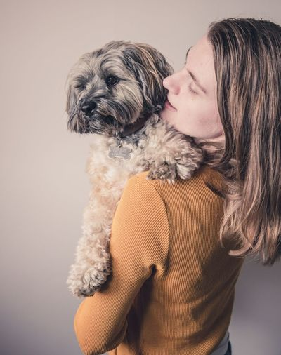 A rear view of a fashionable young girl holding and cuddling her cute pet dog. Dog Pets Domestic Animals Animal Themes Girl Cuddles Cuddling Carrying Cute Pets Cute Fashionable Holding Safe Safety Safe Place Friends Togetherness Best Friends Bff Pet Indoors  Friendship Furry Loveable Puppy