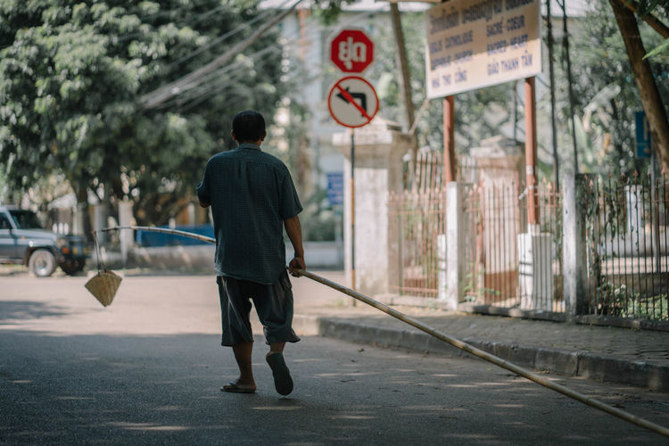 Rear view of man with bamboo walking on road