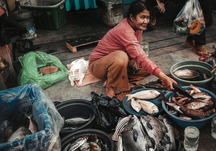 High angle view of woman sitting at fish market