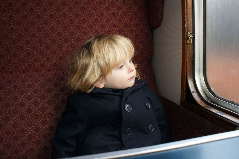 Child sitting on seat by window in train