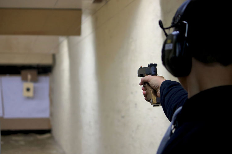Shooting practice Activity Aiming Ear Protection Gun Handgun Head Protection Indoors  One Person Selective Focus Shooting A Weapon Shooting Practice Social Issues Weapon