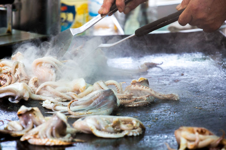 Cropped hands preparing squids