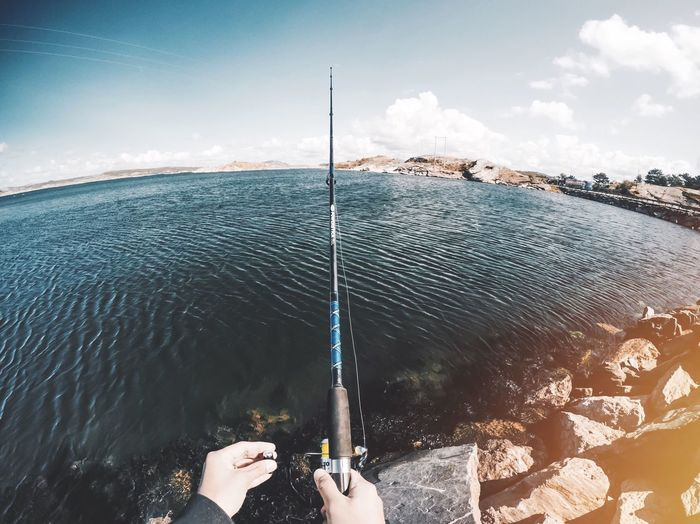 Cropped image of hands holding fishing rod at shore