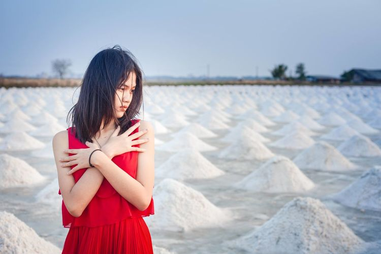 A beautiful woman in a long red dress stands tall among salt fields and blue skies.
