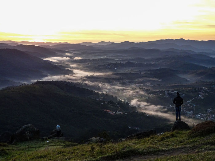 People standing on mountain against sky during sunset