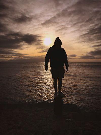 Silhouette man standing on bollard against sea