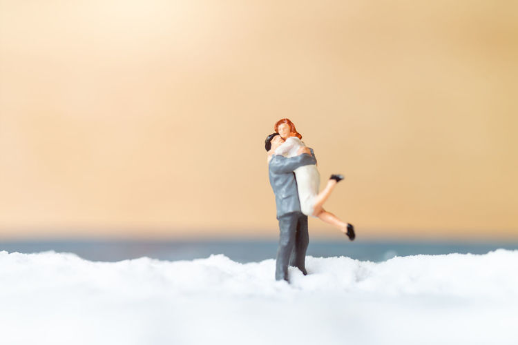 Full length of woman standing in snow against sky during sunset