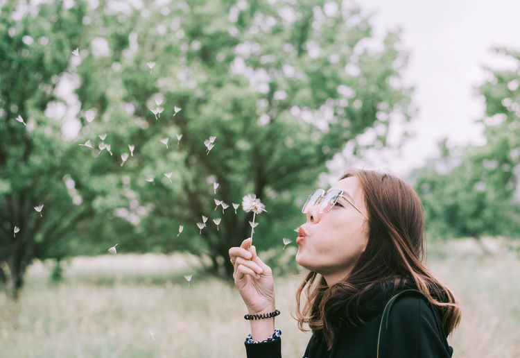 A Woman blowing Enjoy free Blowing Day Flower Flowering Plant Focus On Foreground Fragility Freshness Hair Hairstyle Headshot Leisure Activity Lifestyles Nature One Person Outdoors Plant Portrait Real People Side View Tree Women Young Adult Young Women Summer Road Tripping EyeEmNewHere