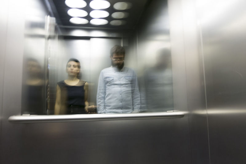 Reflection of man and woman on mirror in elevator