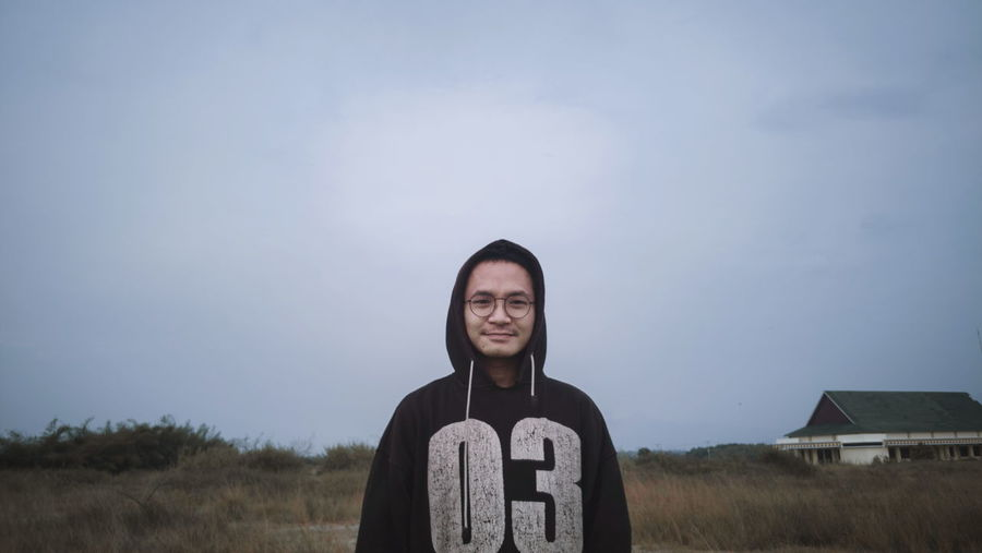 Portrait of young man standing on land against sky