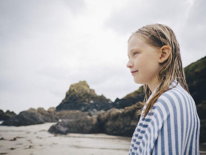 Portrait of teenage girl standing against sky
