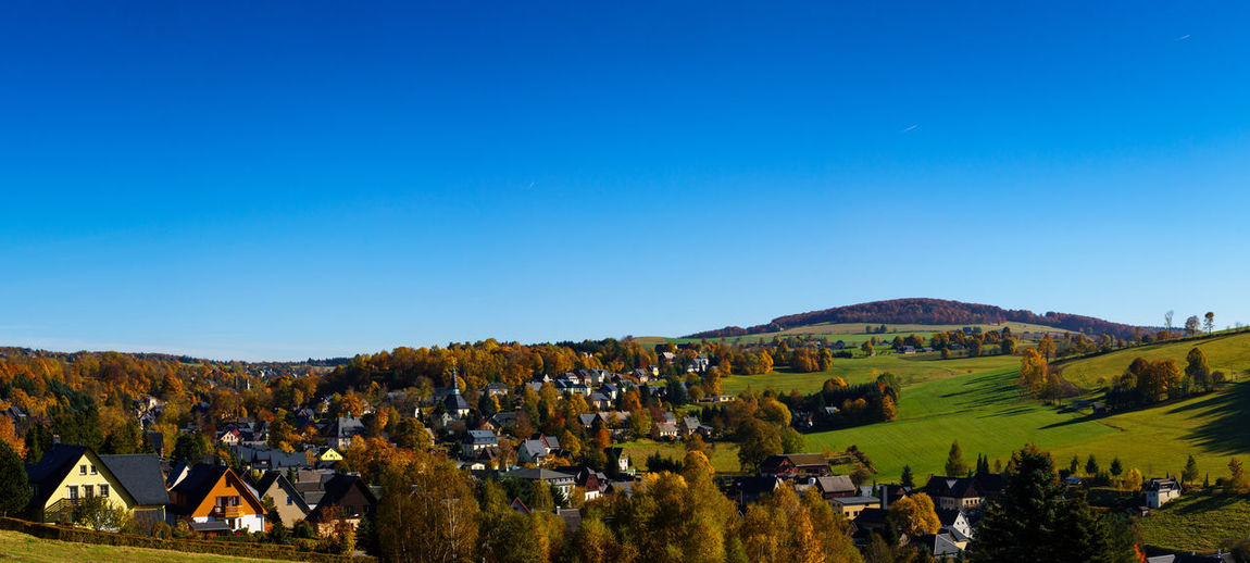 Panoramic view of trees and houses against clear blue sky