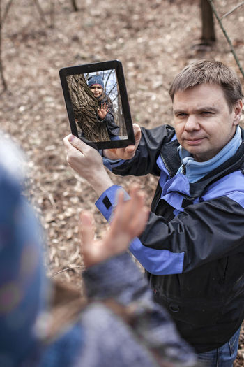 High angle view father showing digital tablet in forest