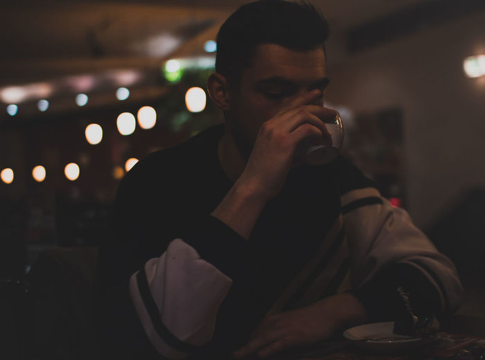 Close-Up Of Young Man Drinking Coffee At Cafe