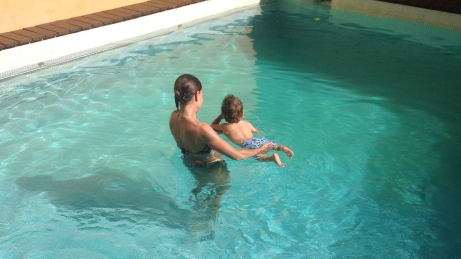 High angle view of mother with son in swimming pool