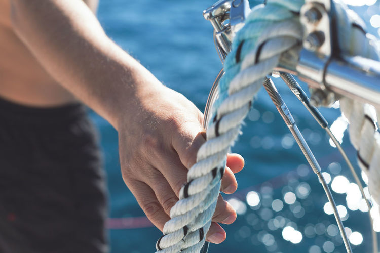 man entering the sea from the yacht Adventure Blue Close-up Day Detail Enjoyment Holiday Human Body Part Human Hand Man Ocean Outdoors People Reflection Rope Sailor Sea Sport Swimming Swimsuit Travel Vacation Water Yacht Yachting
