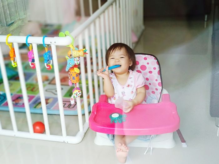 Cute girl sitting on high chair by crib at home
