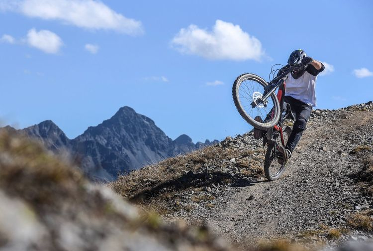 Low angle view of racer riding mountain bike downhill against sky