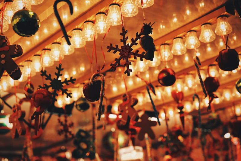 Low angle view of illuminated light bulbs and christmas decorations on ceiling