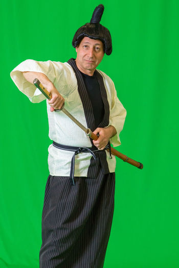 Portrait of man dressed as samurai against green background