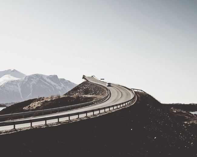 Road on mountain against clear sky during foggy weather