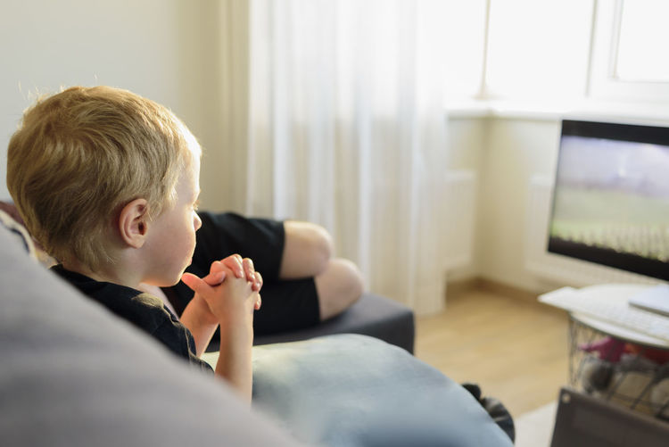 Boy watching tv in living room at home