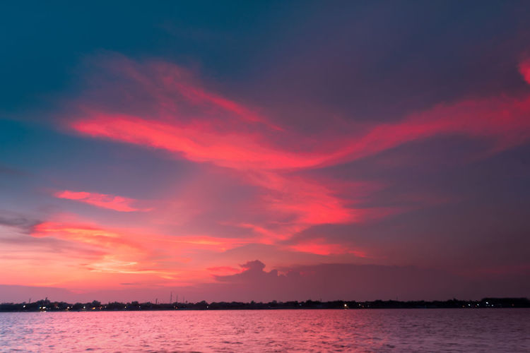 Scenic view of river against dramatic sky during sunset