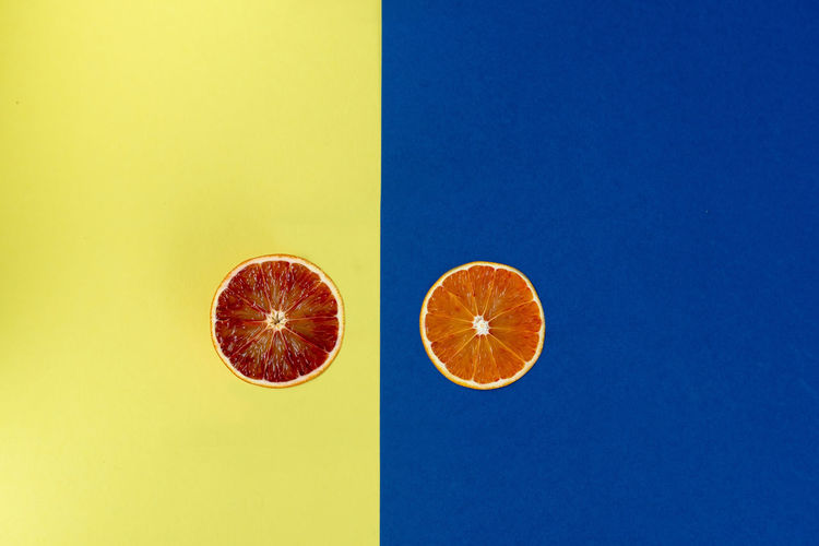 Flat lay of orange fruit slices on yellow and blue paper background No People Copy Space Studio Shot Indoors  Background Orange - Fruit Orange Color Orange Fruit Food Vitamin View Top View Flat Lay Flatlay Flat Yellow Creative Healthy Eating Healthy Eating Cut Design Fresh Juicy Modern Natural Sweet Diet Summer Half Nature Template Citrus  Style Colorful Card Nutrious Ripe SLICE Isolated Abstract Art Pattern Banner Freshness Organic Skin Tropical Citrus Fruit Blue Colored Background Food And Drink Wellbeing Cross Section Still Life Blue Background