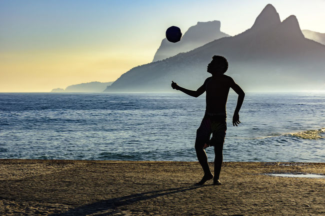Soccer player in front of the sea during sunset Football Ipanema Beach Rio De Janeiro Two Brothers Hill Action Active Beach Beauty In Nature Leisure Activity Lifestyles Nature Outdoor Outdoors Sea Silhouette Sky Soccer Soccer Player Sport Summer Sunset Tropical Unrecognizable Person Water Young Man